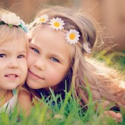 portrait of two happy adorable little  girls sisters on green grass at sunny summer day